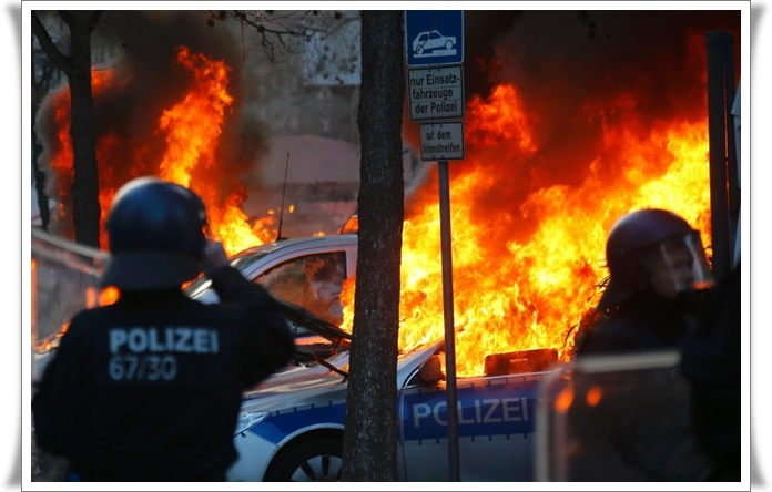German police cars set on fire by anti-capitalist protesters burn near the new ECB headquarters in downtown Frankfurt