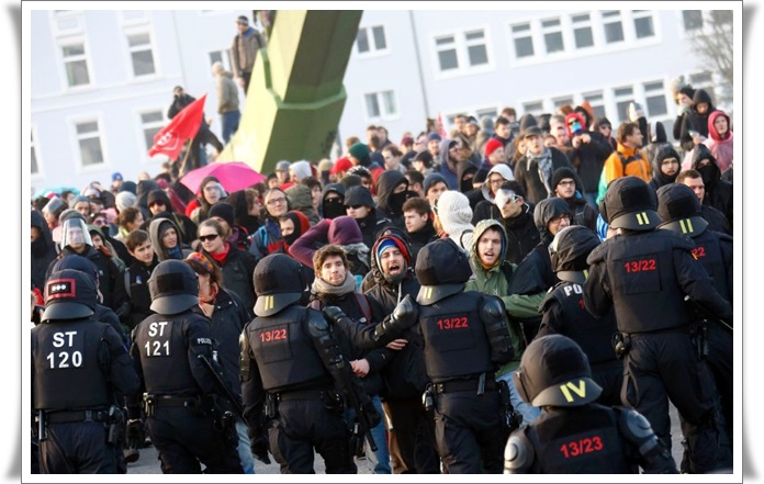 Policemen stand in front of 'Blockupy' anti-capitalist protesters near the ECB building before the official opening of its new headquarters in Frankfurt